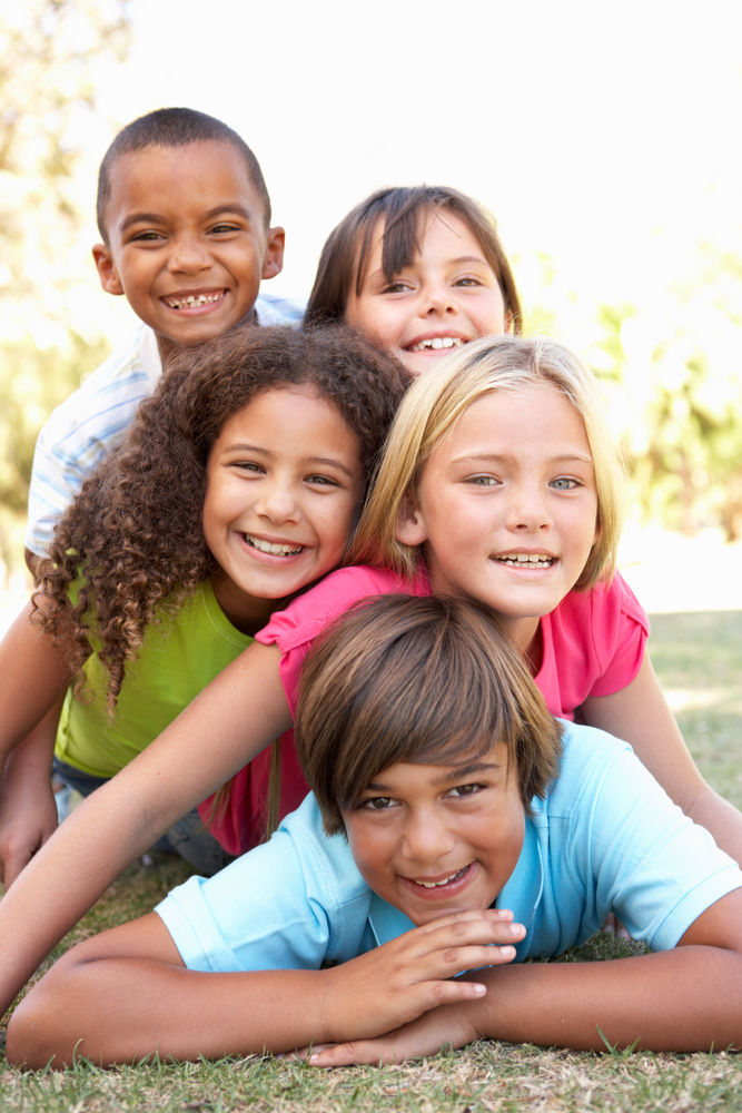 happy multi ethnic children in colorful t shirts lying on grass and smiling - Images For Children